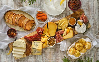 A festive holiday feast for small groups with Ontario cheeses and meats on a wooden board with Ancho Pepper Candied Nuts, Cheese Bread & Homemade Cinnamon Raisin Toast.
