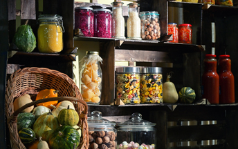A pantry lined with glass jars filled with pastas, beans and other staples.