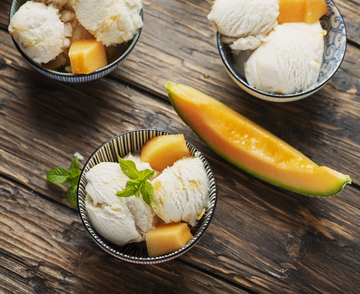 Three small grey bowls with freshly churned ice cream, with seasonal fruit, placed on a rustic wooden table
