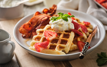 A white plate with three buttermilk bacon waffles, two pieces of crispy bacon, topped with fresh strawberries and creme fraiche.