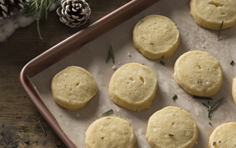 Eight cheddar and rosemary shortbread cookies are on parchment paper on a cookie sheet