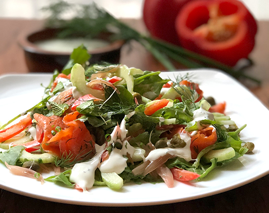 A white plate filled with fresh greens, tomatoes topped with Ontario trout gravlax with a chive cheese dressing.