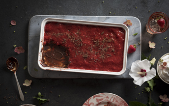 A rectangular metal baking pan with chocolate semi freddo with strawberry sauce sitting on a marble slab