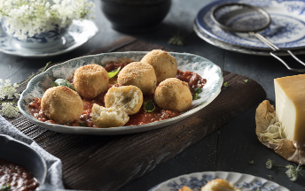 A dark grey bowl that has four double cheese arancini balls in tomato sauce