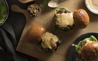 A wooden cutting board with two gouda beer cheeseburgers, with the top bun askew displaying the cheese on the burger