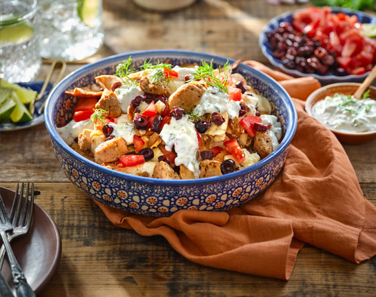 A colourful blue and red bowl on a brown cloth placemat, filled with Greek-Style Chicken Gyro Nachos.