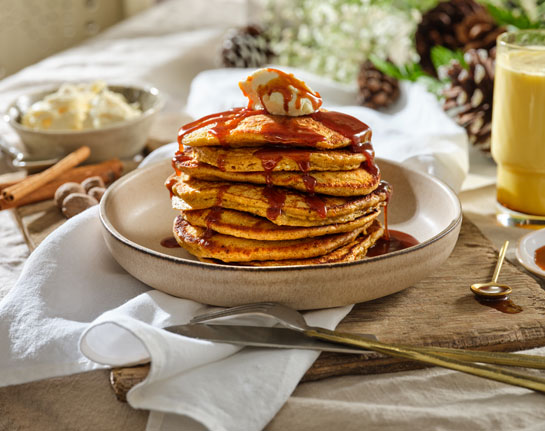 A stack of 8 eggnog pancakes on a beige stoneware plate, dripping with caramel sauce and topped with mascarpone.