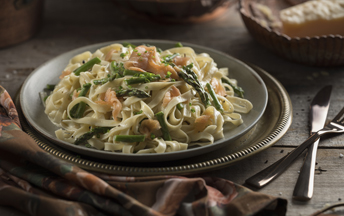 A dark grey plate with lemon asparagus fettucine sitting on a rustic wooden table