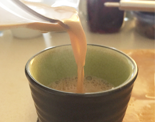 A mug being filled with milky chai.