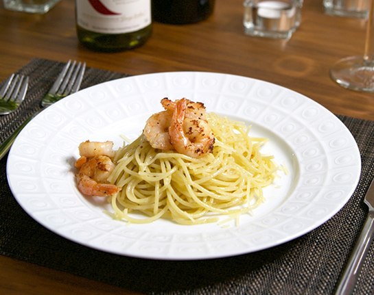 A white plate with a serving of pasta, topped with shrimp