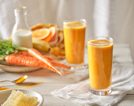 Two glasses of smoothies, on a white tablecloth with carrots in the background.