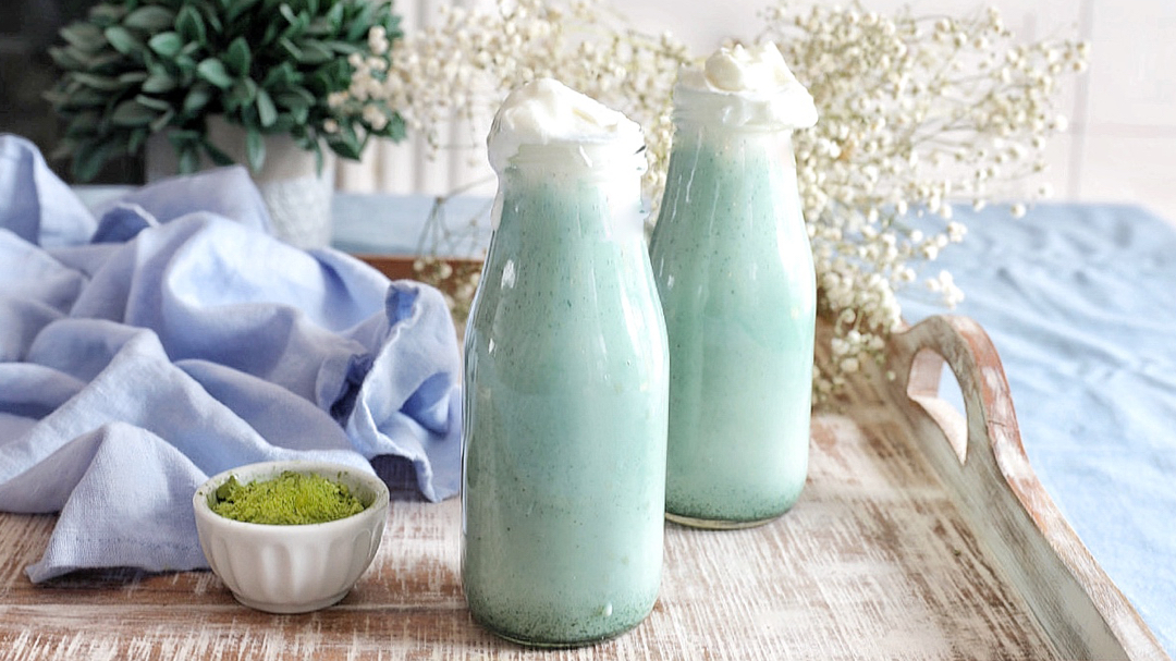 Two milk bottles with green/blue smoothie with whipped cream on top on serving tray.