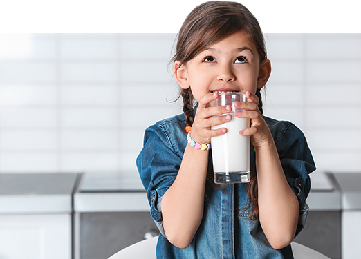 a young girl holds a glass of milk
