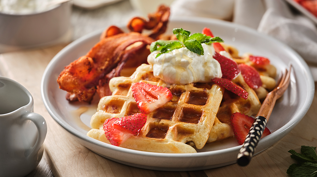Buttermilk bacon waffles topped with bacon slices, dollop of whipped cream and strawberries.