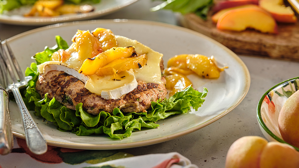 Open face turkey burger on bed of lettuce topped with peach slices and brie cheese.