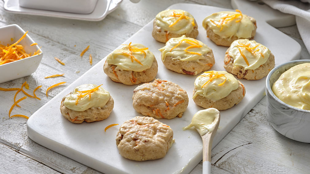Orange Carrot cookies with orange cream cheese frosting on white serving board with white spoon.