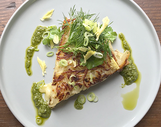 A white plate with a slice of potato rosti topped with salsa verde