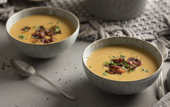 Two grey soup bowls with creamy sweet potato soup with bacon crumbled on top