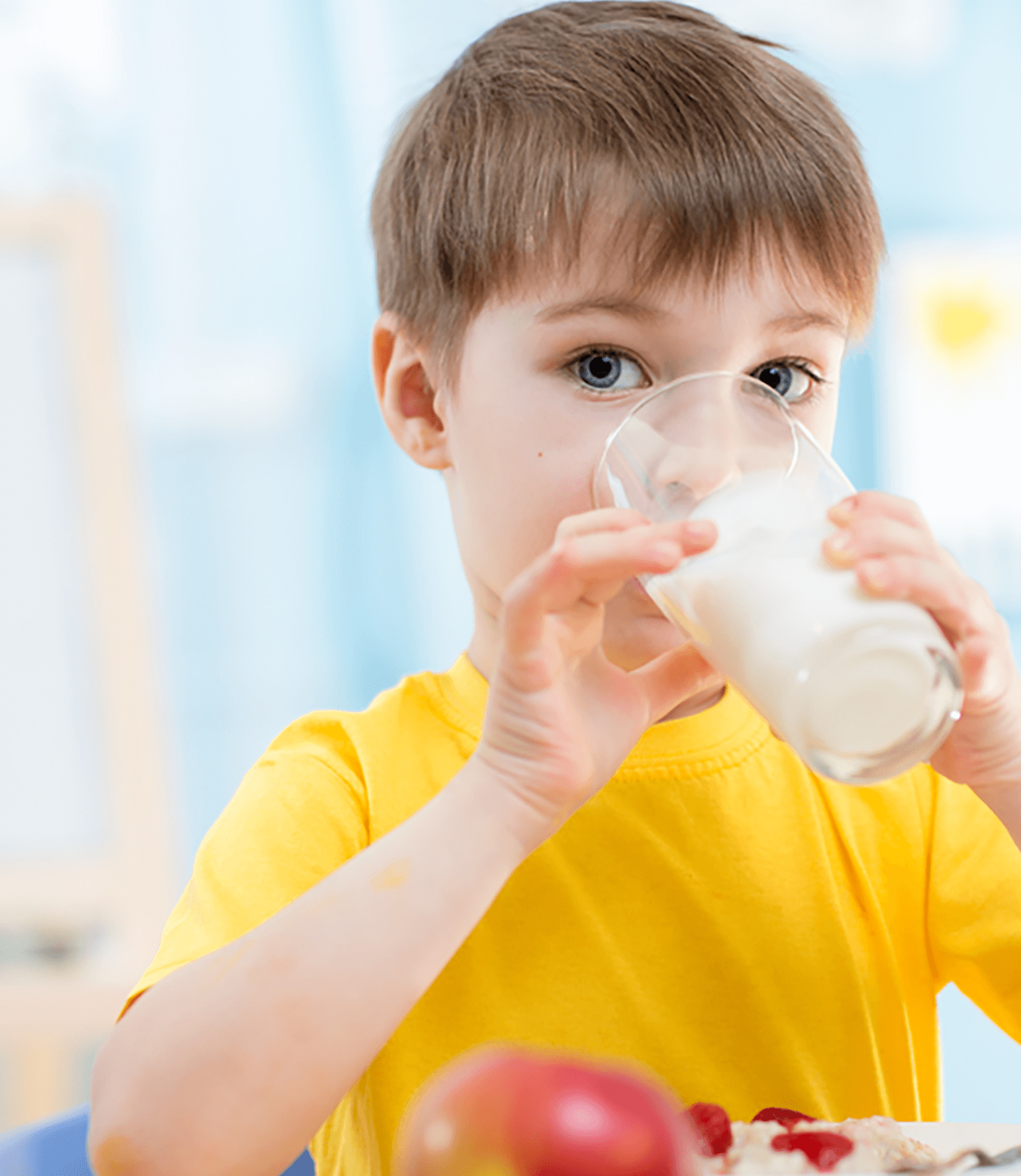 A young boy drinks milk from a glass