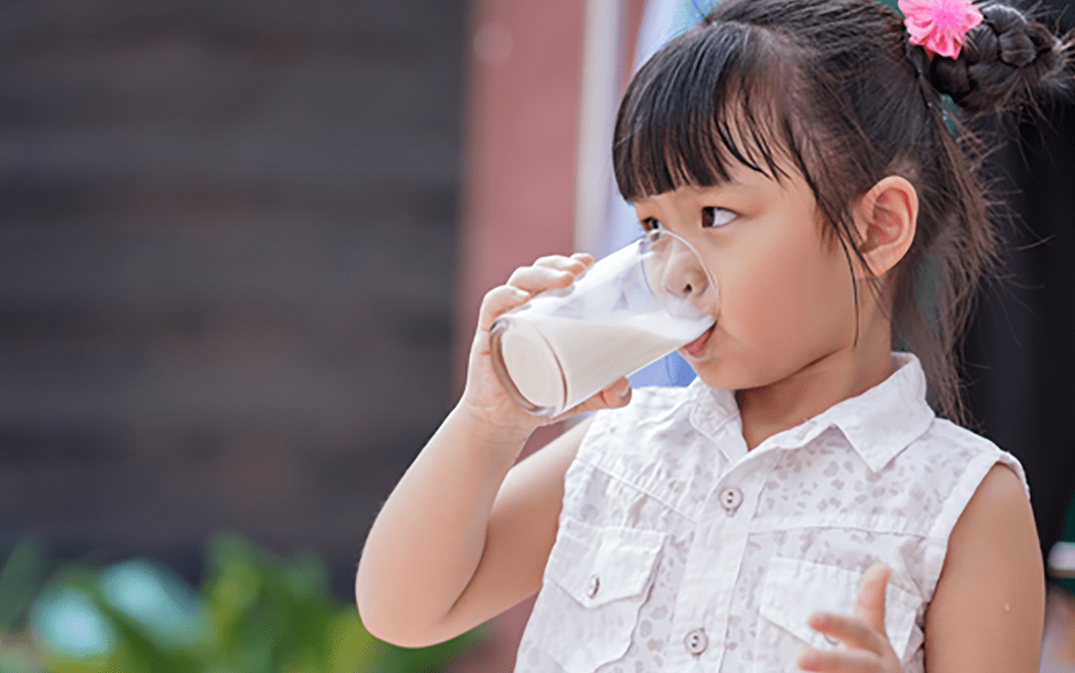 A young girl drinks milk from a glass
