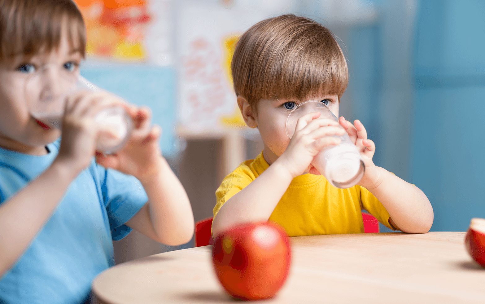 Two elementary school children drink milk from glasses