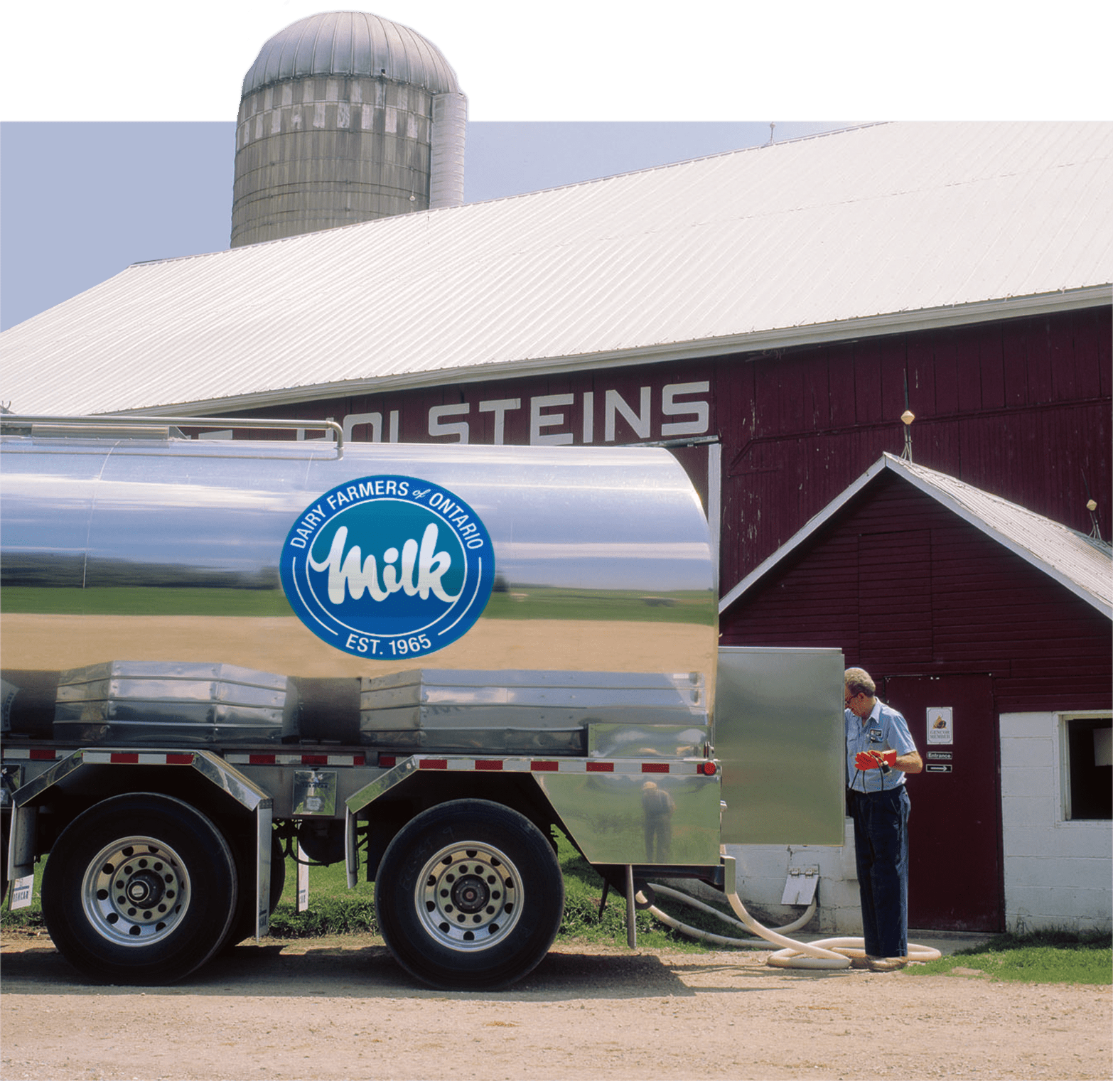 A milk tanker being filled at a farm